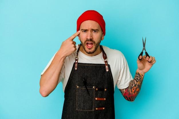 Jeune homme de coiffeur tatoué isolé sur fond bleu montrant un geste de déception avec l'index.