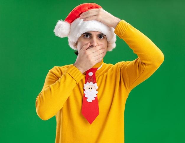 Jeune homme en col roulé jaune et bonnet de noel avec cravate drôle avec la main sur sa tête couvrant la bouche avec la main debout sur le mur vert