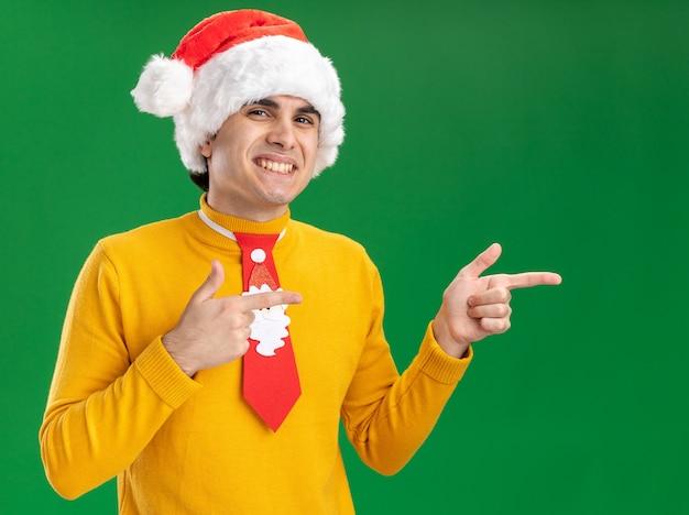 Jeune homme en col roulé jaune et bonnet de noel avec cravate drôle regardant la caméra en souriant joyeusement pointant avec l'index sur le côté debout sur fond vert