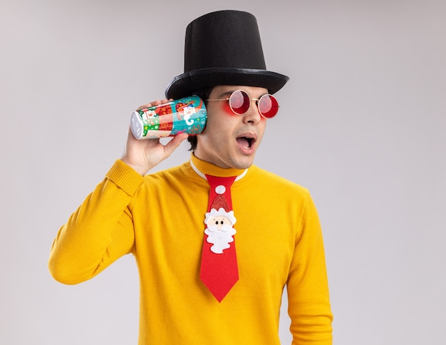 Jeune homme à col roulé jaune et lunettes portant un chapeau noir et cravate drôle tenant une tasse de papier coloré sur son oreille en essayant d'écouter debout sur fond blanc