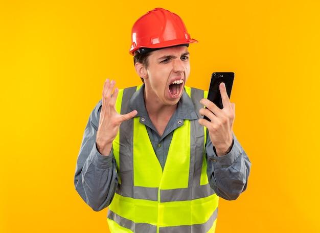Jeune homme en colère de constructeur en uniforme tenant et regardant le téléphone