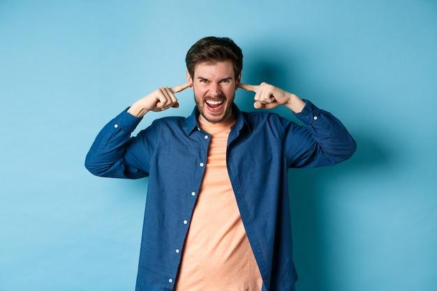 Un jeune homme en colère ferme les oreilles pour bloquer le son ennuyeux et crie à la caméra, fronçant les sourcils et l'air furieux, debout sur fond bleu.