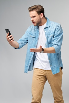 Jeune homme en colère et frustré stressé choqué à l'aide de smartphone