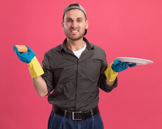Jeune homme en colère de nettoyage portant des vêtements décontractés et une casquette de gants en caoutchouc tenant une plaque et une éponge avec une expression agacée debout sur un mur rose