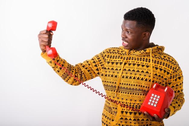 Jeune homme en colère regardant vieux téléphone