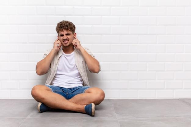 Jeune homme à la colère, stressé et agacé, couvrant les deux oreilles à un bruit assourdissant, un son ou une musique forte