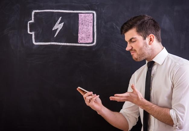 Jeune homme en colère tient son smartphone avec batterie faible.
