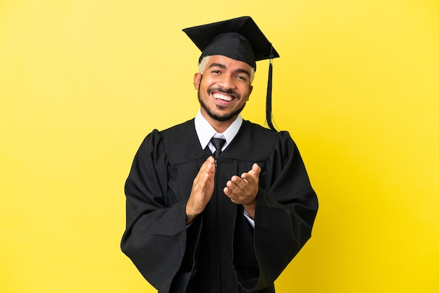 Jeune homme colombien diplômé universitaire isolé sur fond jaune applaudissant après présentation lors d'une conférence