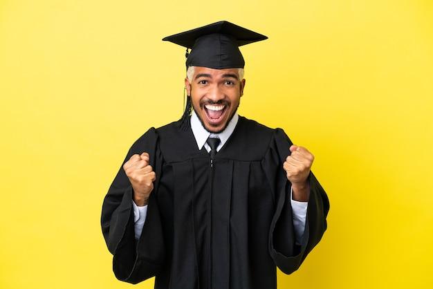 Jeune homme colombien diplômé universitaire isolé sur fond jaune célébrant une victoire en position de vainqueur