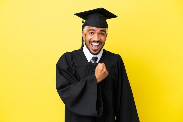 Jeune homme colombien diplômé universitaire isolé sur fond jaune célébrant une victoire