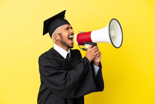 Jeune homme colombien diplômé universitaire isolé sur fond jaune criant à travers un mégaphone