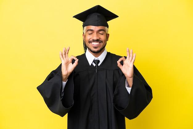 Jeune homme colombien diplômé universitaire isolé sur fond jaune dans une pose zen