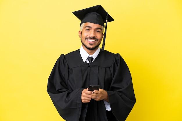 Jeune homme colombien diplômé universitaire isolé sur fond jaune envoyant un message avec le mobile