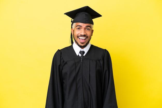 Jeune homme colombien diplômé universitaire isolé sur fond jaune avec une expression faciale surprise