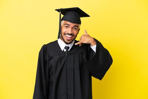 Jeune homme colombien diplômé universitaire isolé sur fond jaune faisant un geste de téléphone. rappelle-moi signe