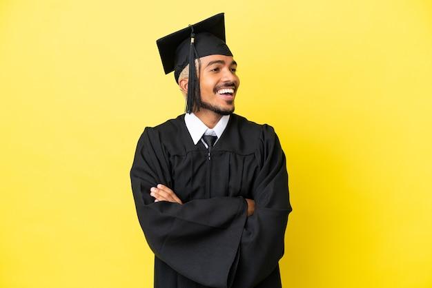 Jeune homme colombien diplômé universitaire isolé sur fond jaune heureux et souriant