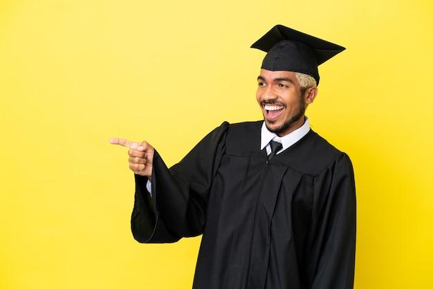Jeune homme colombien diplômé universitaire isolé sur fond jaune, pointant le doigt sur le côté et présentant un produit