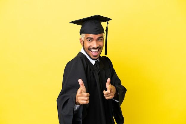 Jeune homme colombien diplômé universitaire isolé sur fond jaune pointant vers l'avant et souriant