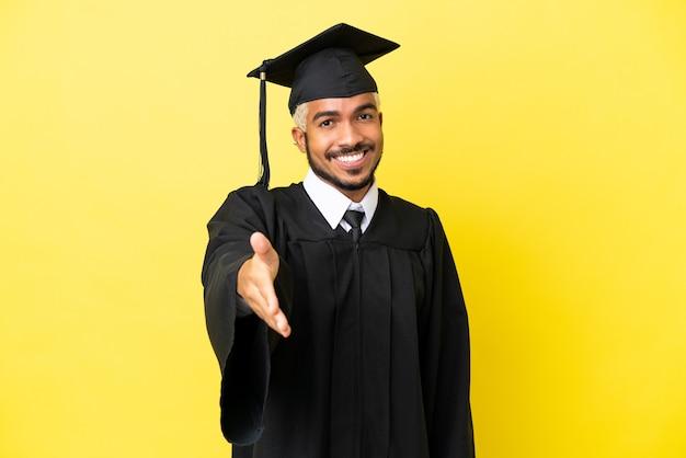 Jeune homme colombien diplômé universitaire isolé sur fond jaune se serrant la main pour conclure une bonne affaire