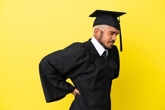 Jeune homme colombien diplômé universitaire isolé sur fond jaune souffrant de maux de dos pour avoir fait un effort