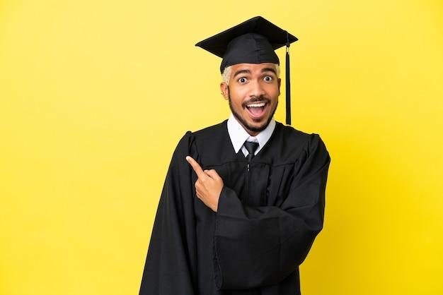 Jeune homme colombien diplômé universitaire isolé sur fond jaune surpris et pointant vers le côté