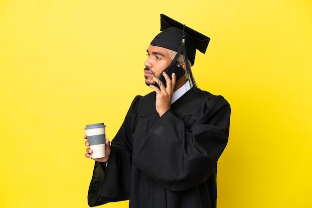 Jeune homme colombien diplômé universitaire isolé sur fond jaune tenant du café à emporter et un mobile