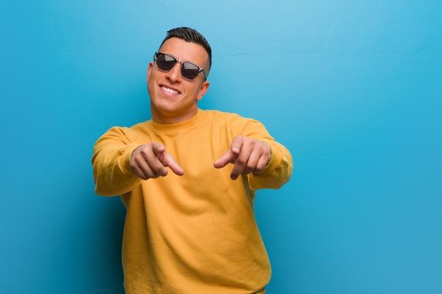 Jeune homme colombien gai et souriant pointant vers l'avant