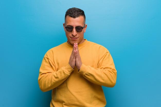 Jeune homme colombien priant très heureux et confiant