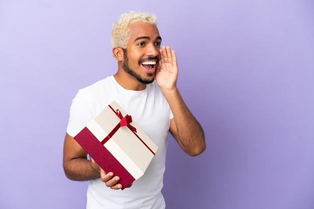 Jeune homme colombien tenant un cadeau isolé sur fond violet criant avec la bouche grande ouverte sur le côté