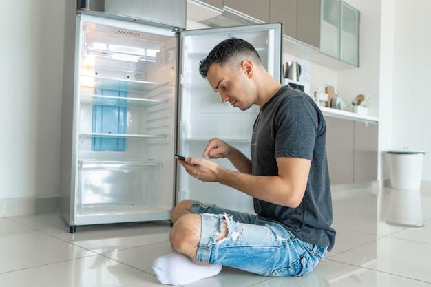 Un jeune homme commande de la nourriture à l'aide d'un smartphone avec réfrigérateur vide