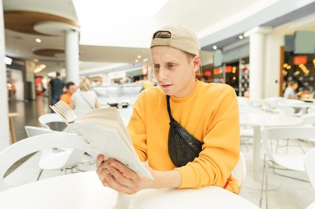 Jeune homme concentré dans un vêtement décontracté lumineux lit un livre dans un café dans un centre commercial.