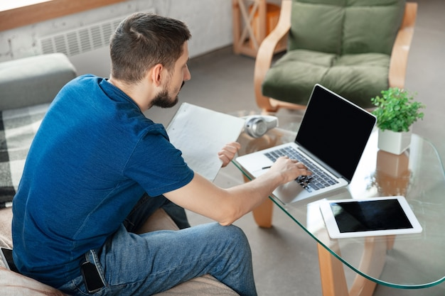 Jeune homme concentré étudiant à la maison pendant des cours en ligne ou des informations gratuites par lui-même. devient chauffeur, manager, photographe en étant isolé, en quarantaine. utilisation d'un ordinateur portable, d'un smartphone, d'un casque.