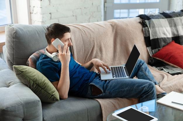 Jeune homme concentré étudiant à la maison pendant des cours en ligne ou des informations gratuites par lui-même