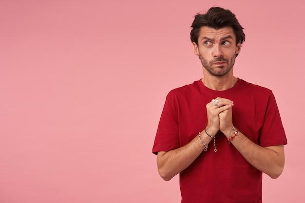 Jeune homme concentré réfléchi avec poils en tshirt rouge garde les mains jointes en position de prière et regardant sur le côté