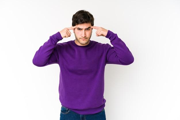 Jeune homme concentré sur une tâche, gardant l'index pointant la tête.