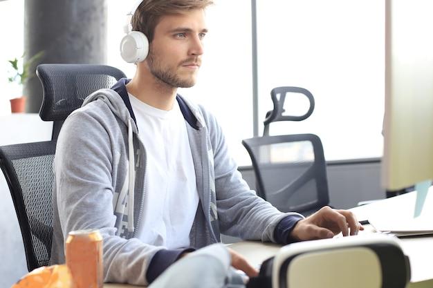 Jeune homme concentré en vêtements décontractés utilisant un ordinateur, une lecture en continu ou une vidéo pas à pas.