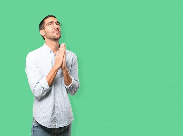 Jeune homme concerné, geste de prière