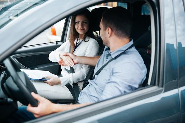 Jeune homme conduisant une voiture avec son instructeur