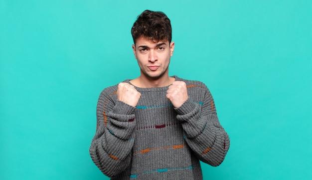 Jeune homme à la confiance, en colère, fort et agressif, avec les poings prêts à se battre en position de boxe