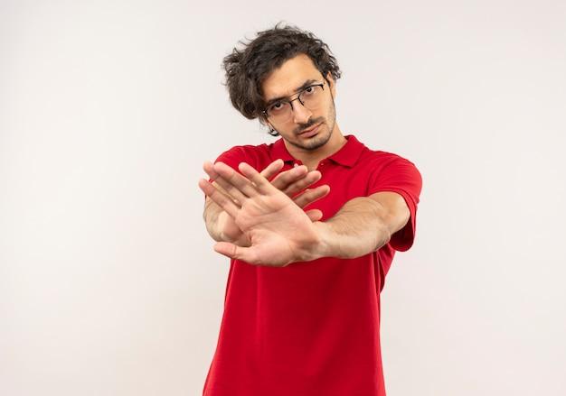 Jeune homme confiant en chemise rouge avec des lunettes optiques fait semblant de pousser avec les mains isolés sur un mur blanc