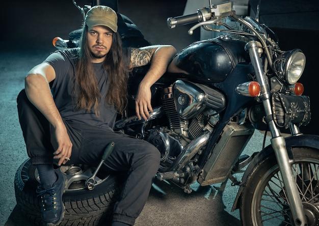 Jeune homme confiant dans un atelier de réparation assis devant une moto rétro portrait de mécanicien automobile