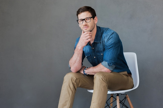 Jeune homme confiant. gentil jeune homme tenant la main sur le menton alors qu'il était assis sur fond gris