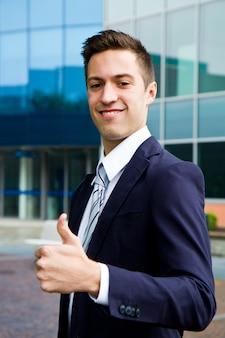 Jeune homme confiant souriant faisant signe pouce en l'air extérieur du bureau