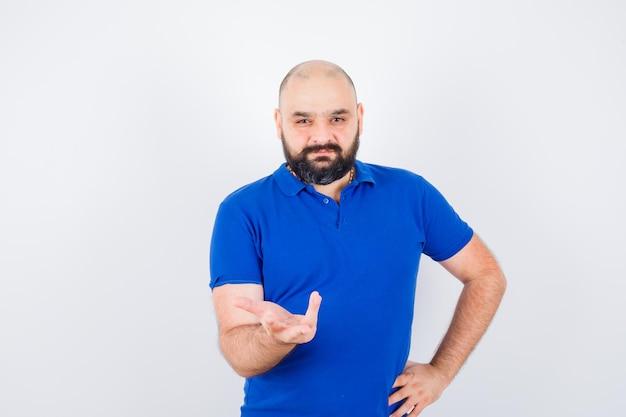 Jeune homme confiant en t-shirt bleu