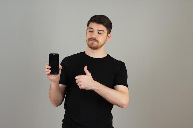 Un jeune homme confiant tenant un téléphone et gesticulant les pouces vers le haut sur un fond gris.