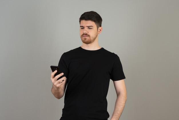 Un jeune homme confiant tenant un téléphone et le regardant sur un fond gris.