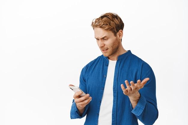 Jeune homme confus et agacé regardant un smartphone, se plaignant sur l'application, lisant un message ridicule dérangeant, levant la main irritée, debout sur un mur blanc