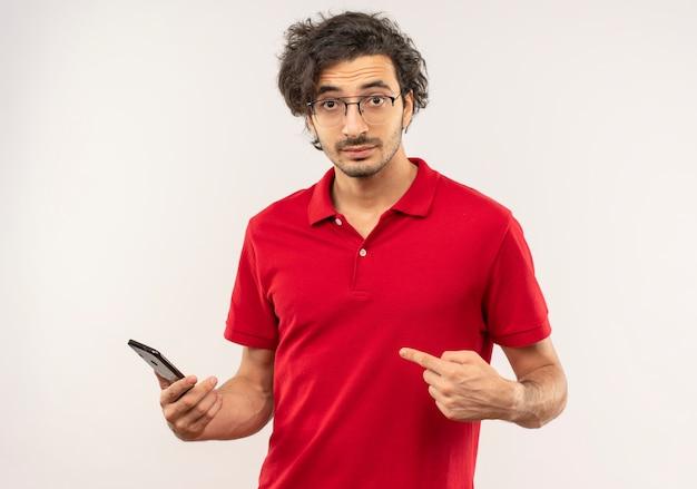 Jeune homme confus en chemise rouge avec des lunettes optiques détient et points au téléphone isolé sur mur blanc