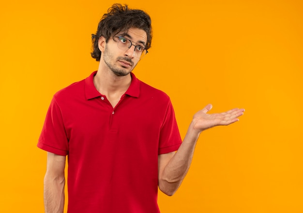 Jeune homme confus en chemise rouge avec des lunettes optiques tient la main droite et regarde côté isolé sur mur orange