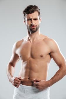 Jeune homme confus insatisfait de l'excès de poids